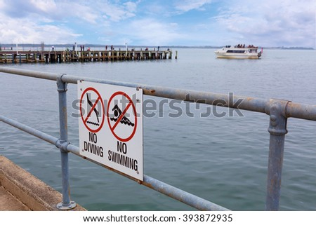No Diving and No Swimming signs on pier railing with ocean water in the background - stock photo