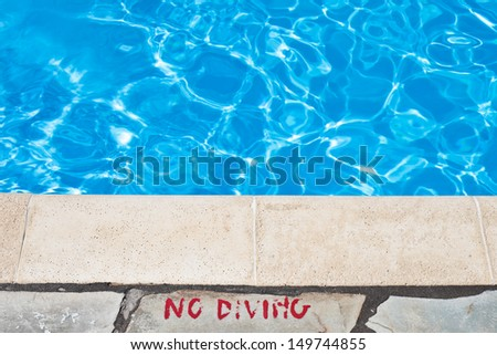 No diving warning at the edge of a swimming pool - stock photo