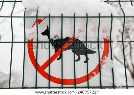 No dogs allowed sign on a fence covered with snow - stock photo