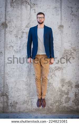 No emotion but in motion. Full length of handsome young man in smart jacket jumping in front of the concrete wall outdoors - stock photo