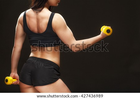 No excuses. Studio shot of a sporty woman exercising with dumbbells on black background. - stock photo