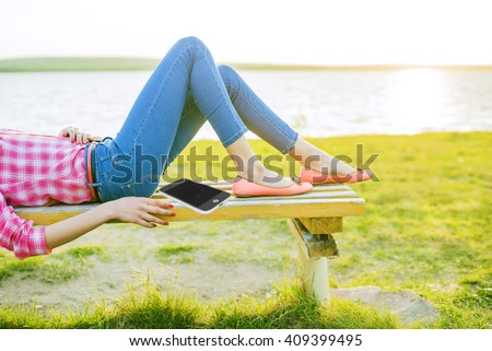 No face. caucasian girl, Woman lie on bench against green fresh grass, sea and sunset sky background . Female on nature spring backdrop. Slim legs in jeans - stock photo