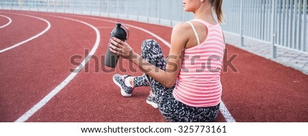 No face. Cute slim young adult girl hold in hand black plastic shaker. Blonde woman sitting on running track and drinking bottled water. Empty sporty space for inscription or other objects and people