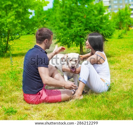 no face Full length portrait of Young  happy Couple sitting with white Dog Labrador at summer park on fresh green grass background against spring trees in perspective Empty copy space for inscription