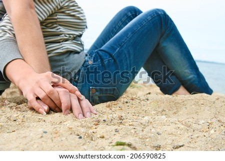 No face image Unrecognizable person Focus on fingers hand Young couple sitting and embracing together on yellow sand beach Textured empty copy space for inscription  - stock photo
