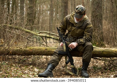 No face. Military man with Kalashnikov rifle outdoor forest