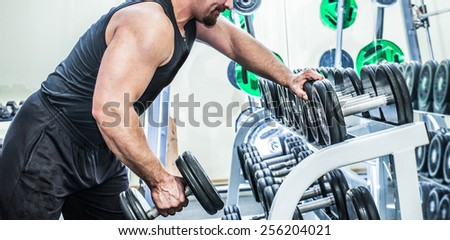 no face Unrecognizable beard person muscular torso man with dumbbell on gray background in studio gym background . Bodybuilder working out biceps with dumbbell Male wear black sport closes - stock photo