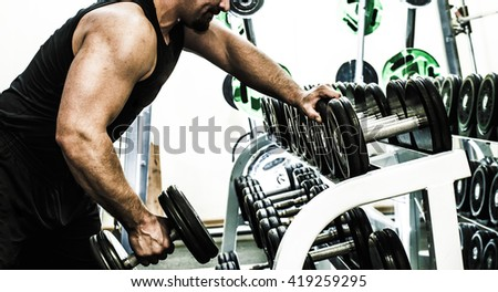 no face. Unrecognizable beard person. muscular torso man with dumbbell on gray background in studio gym background . Bodybuilder working out biceps with dumbbell Male wear black sport closes