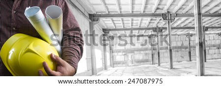 No face Unrecognizable person construction worker man hold in hand blueprint yellow helmet on empty old building inside concrete warehouse background Copy Space for inscription Idea concept of safety - stock photo