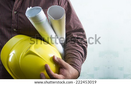 No face Unrecognizable person construction worker man holding in hands blueprint and yellow helmet on green texture wall with wallpaper background Empty copy space for inscription - stock photo