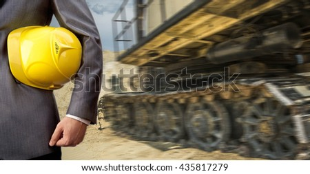 No face Unrecognizable person. engineer hold in hand  yellow helmet for workers security over yellow tractors or excavator - stock photo
