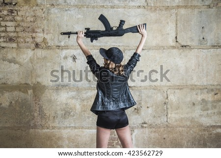 No face. unrecognizable person of young sexy woman in a leather jacket and sexual brassiere with a Kalashnikov in her hand. Girl stand against concrete wall. Back view - stock photo