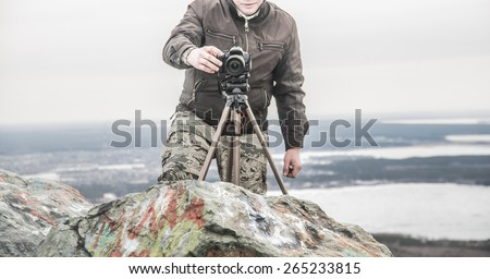 No face Unrecognizable person Professional photographer shooting Finger push button Man stand on stone mountain high in heaven against horizon with town and river or lake Photo Camera stand on tripod - stock photo