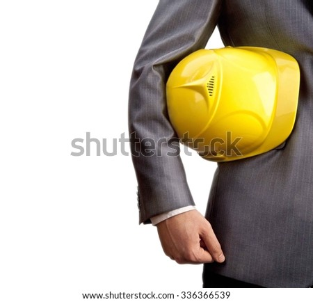No face Unrecognizable person. torso of engineer or worker hold in hand yellow helmet for workers security isolated on white background. Man wear business suit and white shirt  - stock photo
