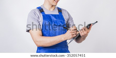 No face. Unrecognizable person. Worker , engineer writing pen in folder. Isolated on white or gray empty background. Empty copy space for inscription, people or objects. Man wear blue uniform - stock photo