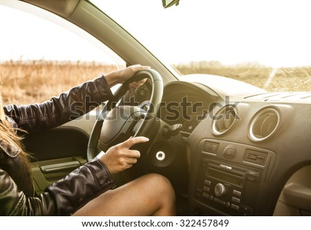 No face. woman hands on wheal in the new car - indoor on yellow sunset sky background Sexy girl drive along wheat summer field Empty copy space for inscription Naked legs