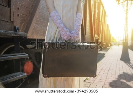no face. Woman with suitcase stand on stair of wagon. Railway station against retro vintage old locomotive in perspective.Young adult girl hold in hands case. Female wear gloves and dress - stock photo