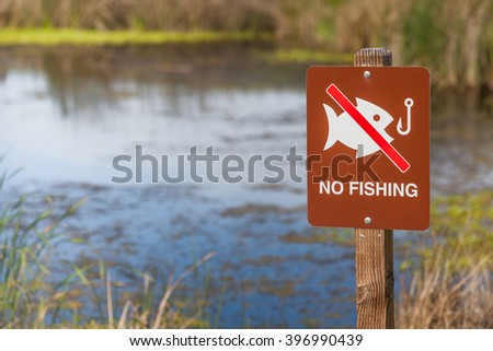 No fishing sign in front of a pond. - stock photo