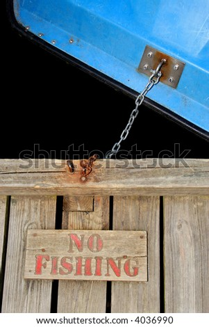 No fishing sign with boat chained to dock - stock photo