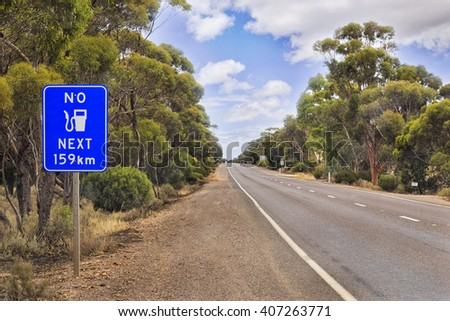 No fuel sign along Eyre Highway in South Australia. Natural eucalyptus woods without developed infrastructure and motoring service under blue cloudy sky