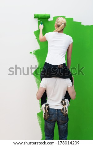 No ladder - no problem - as a clever young couple resort to a piggy back ride with her sitting on her husbands shoulders in order to reach the top of the wall, view from behind - stock photo