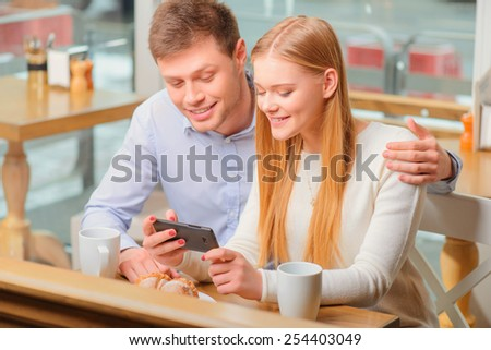 No minute without technologies. Beautiful young loving couple bonding to each other and looking at mobile phone while sitting in cafe together - stock photo