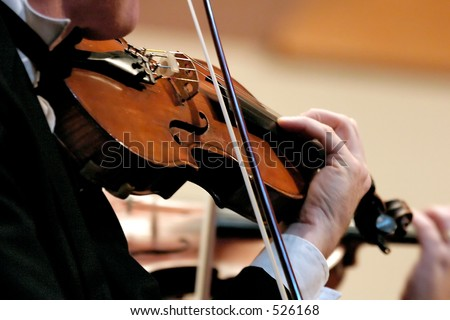 No Model here.  Closeup of musician playing the violin during a symphony - soft fous - stock photo