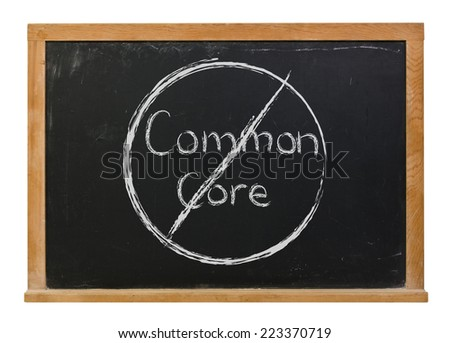 No more common core written in white chalk on a black chalkboard isolated on white - stock photo