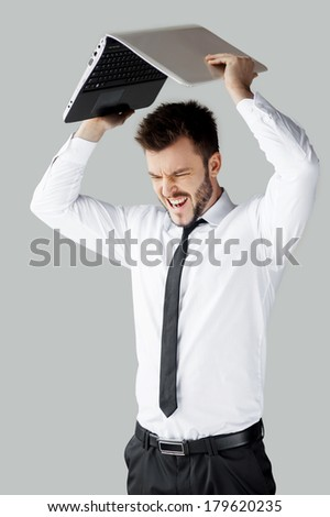 No more working! Furious young man in formalwear trying to break a laptop while standing against grey background - stock photo