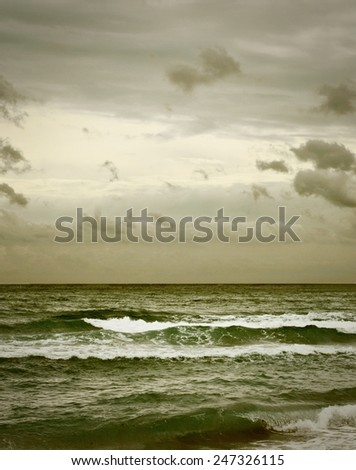 No one is on this empty, lonely beach scene on a stormy day with instagram style filter applied.  Vertical image with dark, stormy seas and an interesting overcast and cloudy sky above - stock photo