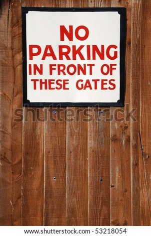 no parking in front of these gates vintage sign at a wooden fence background
