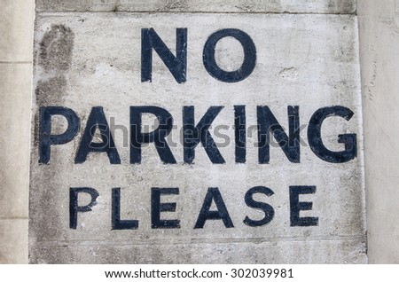 NO PARKING PLEASE painted onto an old textured wall. - stock photo