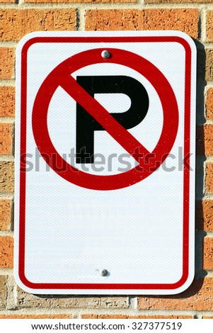 No Parking sign on a brick background.  There is ample copy space in the image.