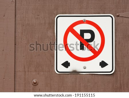 No parking sign on brown wooden door