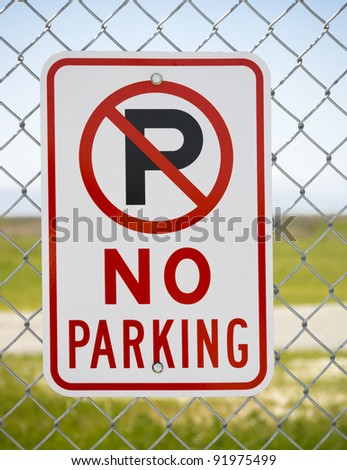 No Parking sign on fence by open countryside - stock photo