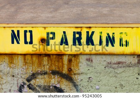 No Parking sign painted on a grungy old wall on an abandoned urban building. - stock photo