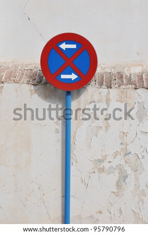 No Parking Traffic Sign in front of Grungy Cement Wall on Sunny Day in Spain Europe - stock photo