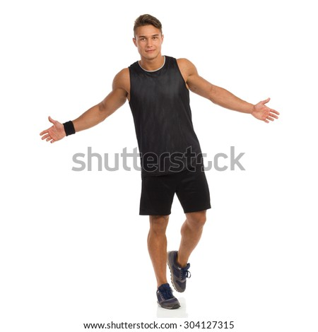 No Problem. Young man in sport black shirt and shorts walking with arms outstretched. Front view. Full length studio shot isolated on white. - stock photo