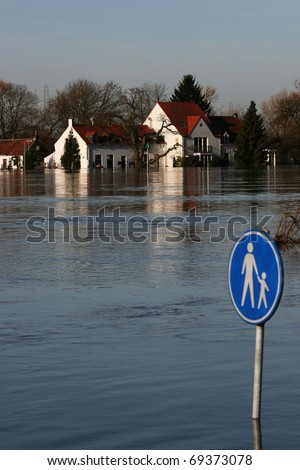 No school today!  A river has flooded it's bank and a house/restaurant.  There's a sign with a adult and a child on it and this is deep under water. - stock photo