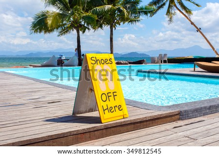 No shoes label nearly pool - An iconic sign prohibits the use of no shoes. - stock photo