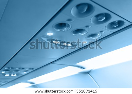 No Smoking and Fasten Seat belt Sign Inside an Airplane. Blue toned  - stock photo