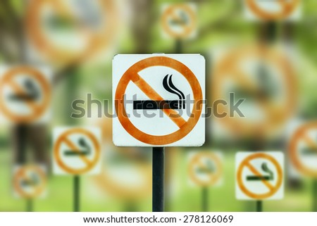 no smoking metal sign on abstract green background. - stock photo