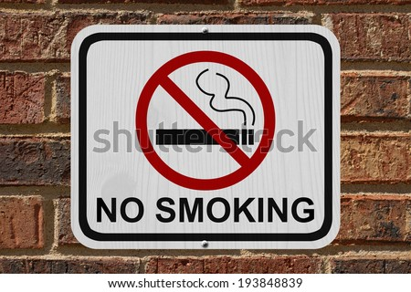 No Smoking Sign, An red and white sign with cigarette icon and not symbol with text No Smoking on a brick wall - stock photo
