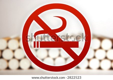 No smoking sign in front of blurry cigarettes. - stock photo
