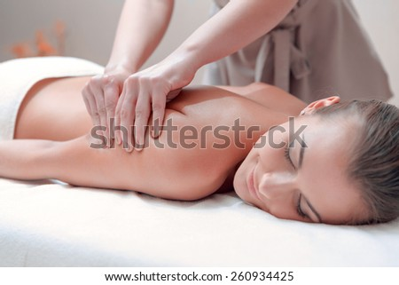 No stress. Beautiful young woman lying on front and keeping eyes closed while massage therapist massaging her back in spa - stock photo