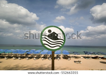 No swimming sign Chairs tables umbrellas tanning life by the beach in Southeast Asia sea view