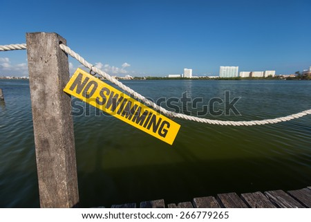 No swimming sign on wooden tablet near lagoon  - stock photo