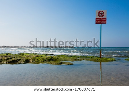 No swimming warning sign, Hebrew, Arabic, English in the beach of Tel Aviv Israel - stock photo