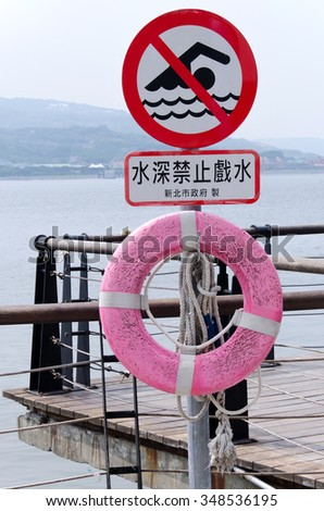 No swimming warning sign on a wooden stick by the pier. A pink life ring and ropes hung under the sign.  Chinese text meaning: Danger. Deep waters. - stock photo