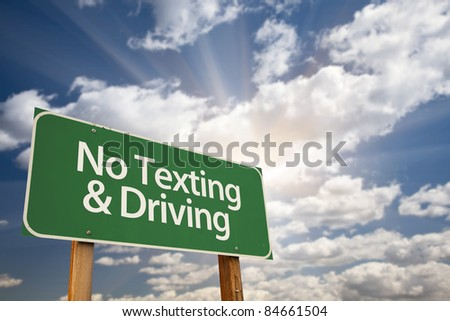 No Texting and Driving Green Road Sign with Dramatic Sky, Clouds and Sun. - stock photo